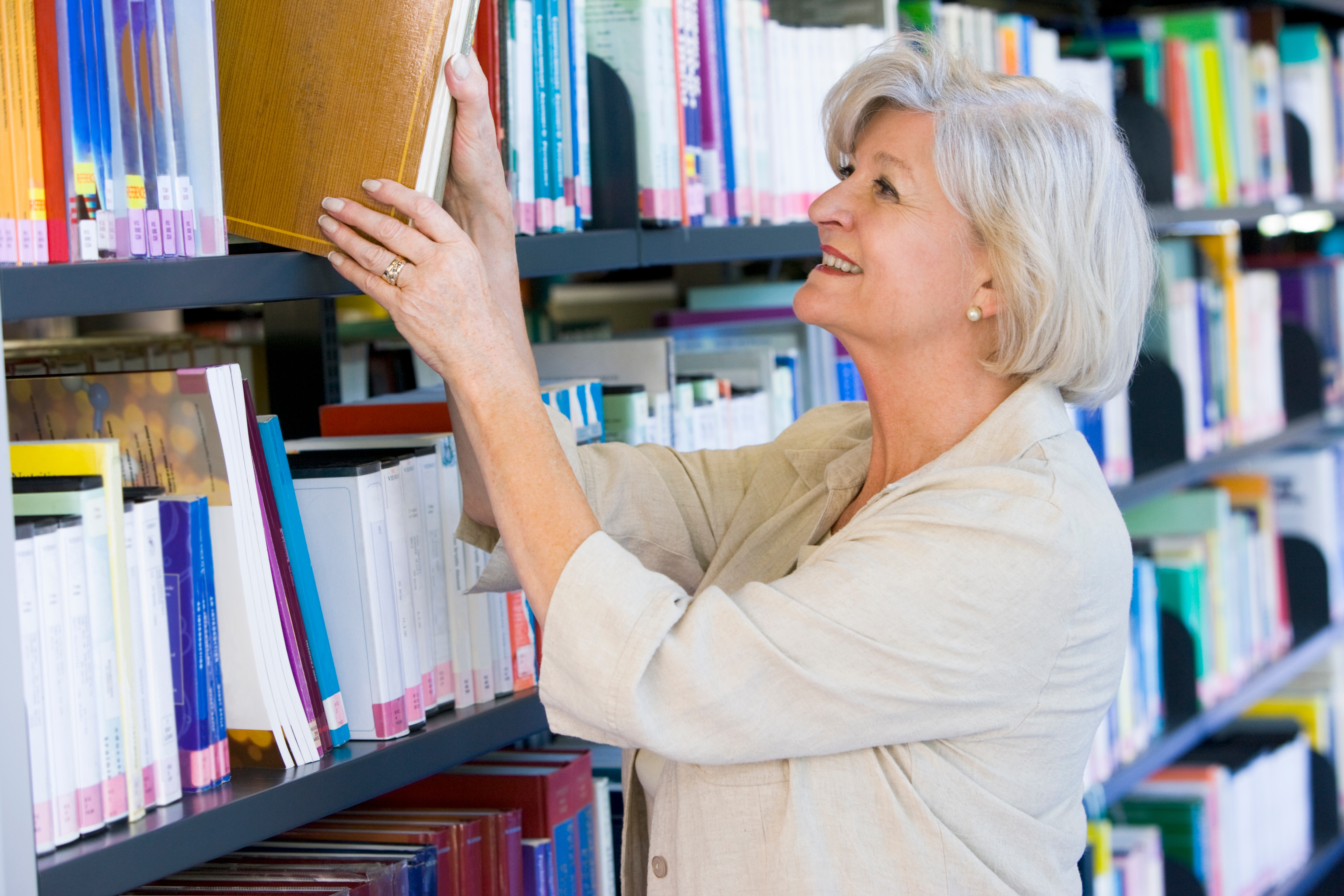 senior-woman-pulling-a-library-book-off-shelf_rKwlMCHo